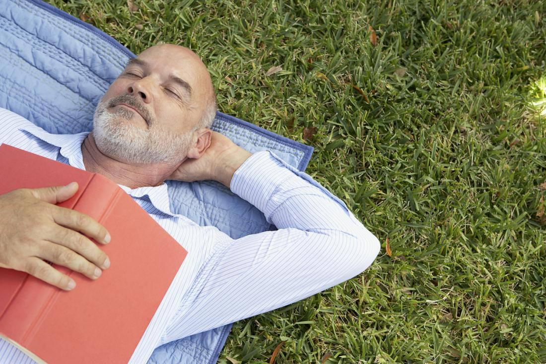 older man sleeping with book on chest