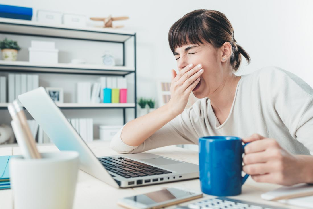 Woman at desk with hot drink yawning