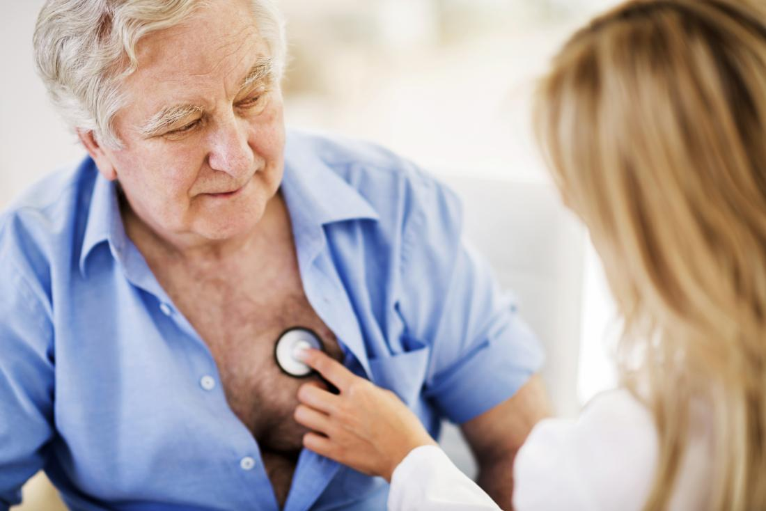 doctor checks older man's heartbeat