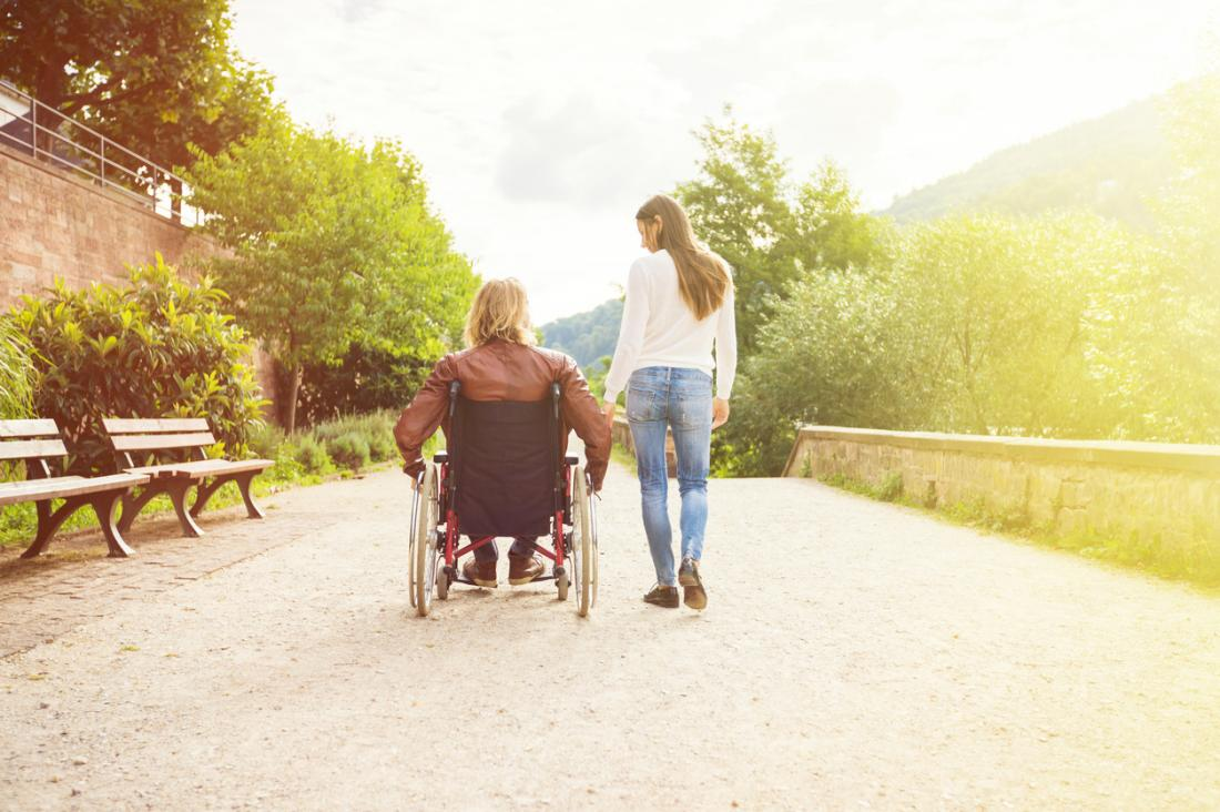 couple walking with man in wheelchair