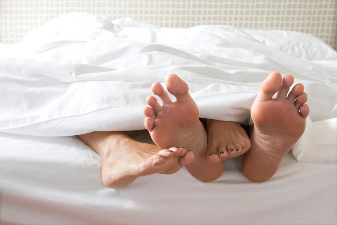 two pairs of feet at the end of a bed