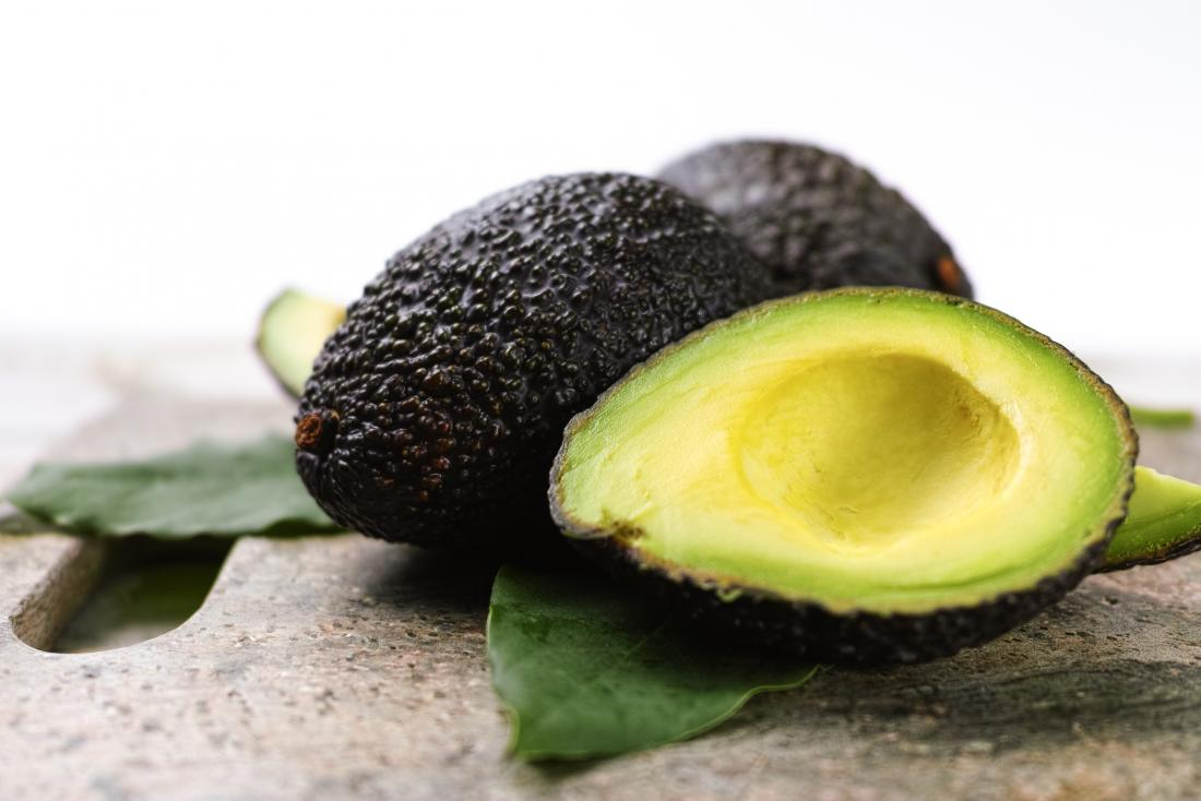 Avocados piled on stone slab as a food that will not raise blood glucose levels.