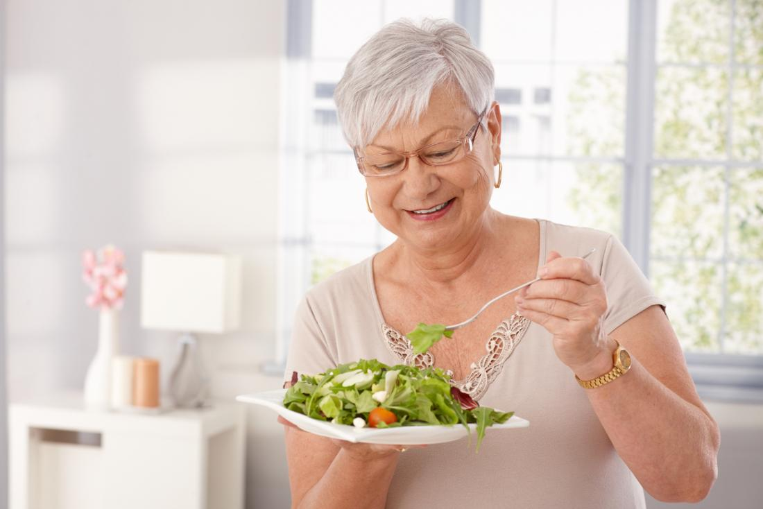 an older woman eating a salad