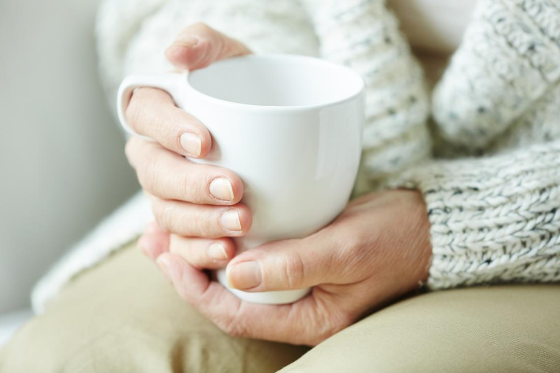 older persons hands with hot drink