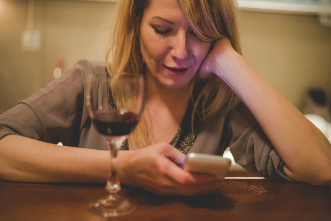 woman holding phone with glass of red wine on the table
