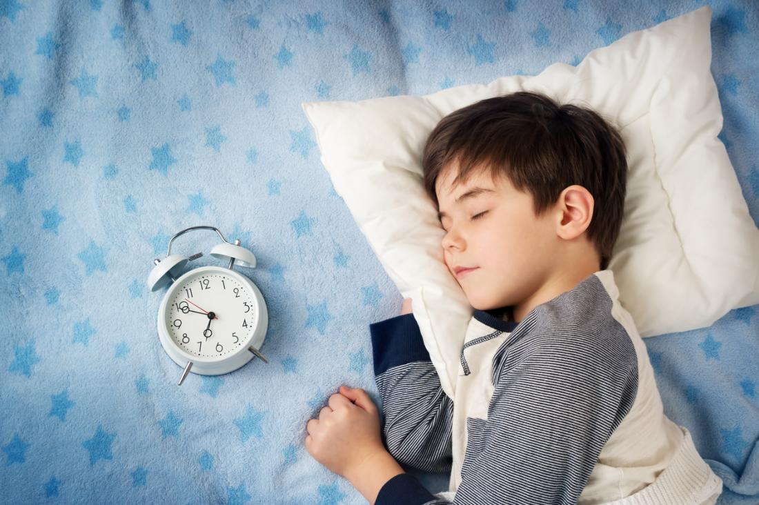 child sleeping with clock