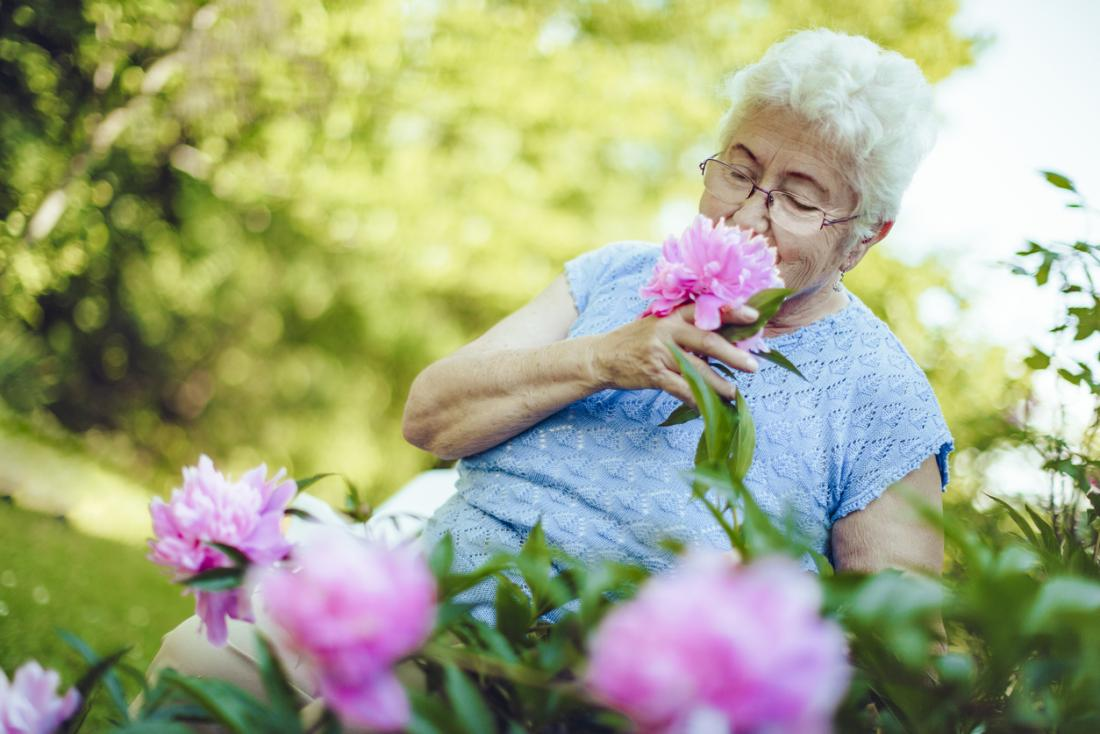 older woman smelling a peony