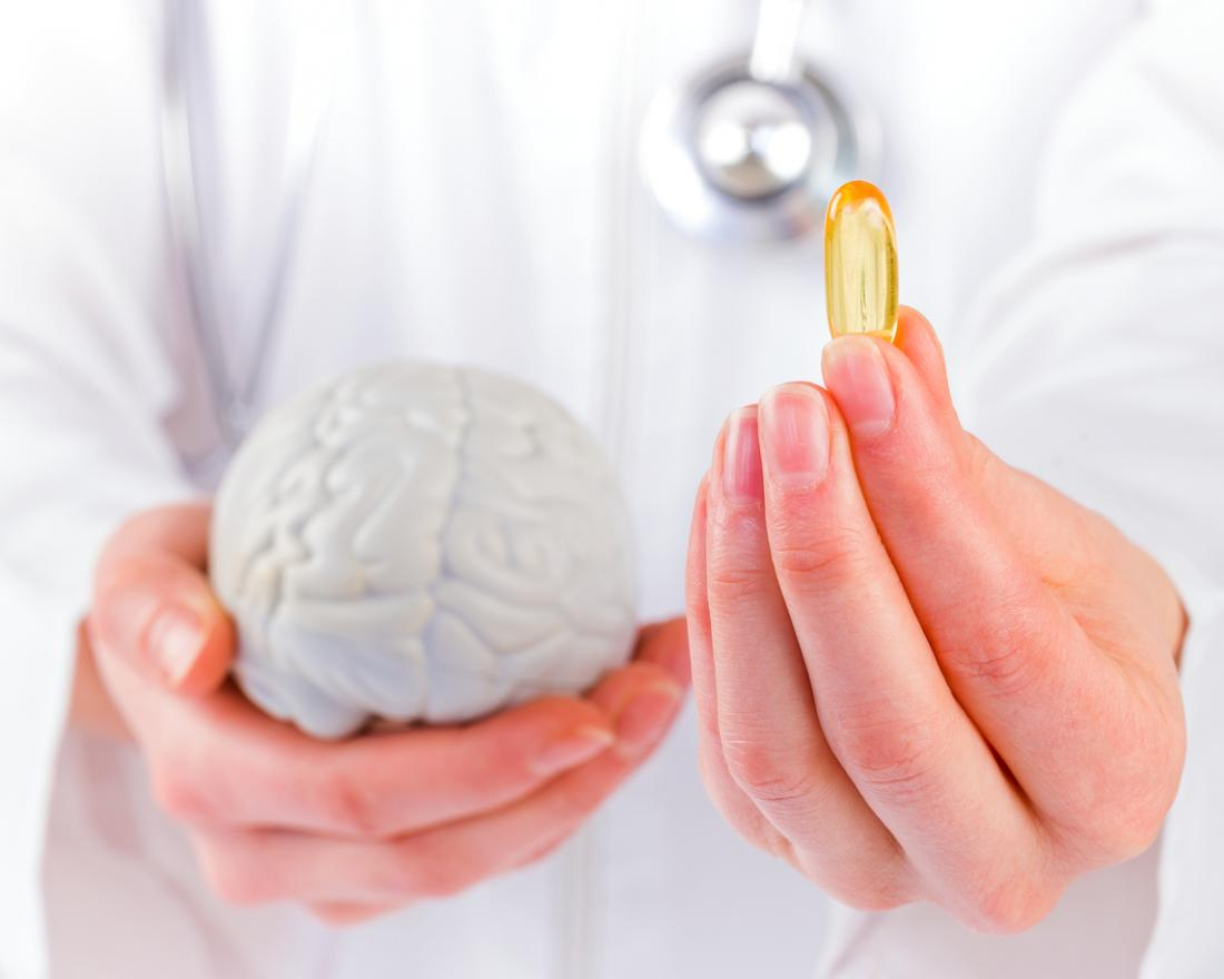 a doctor holding a fish oil supplement and a brain model