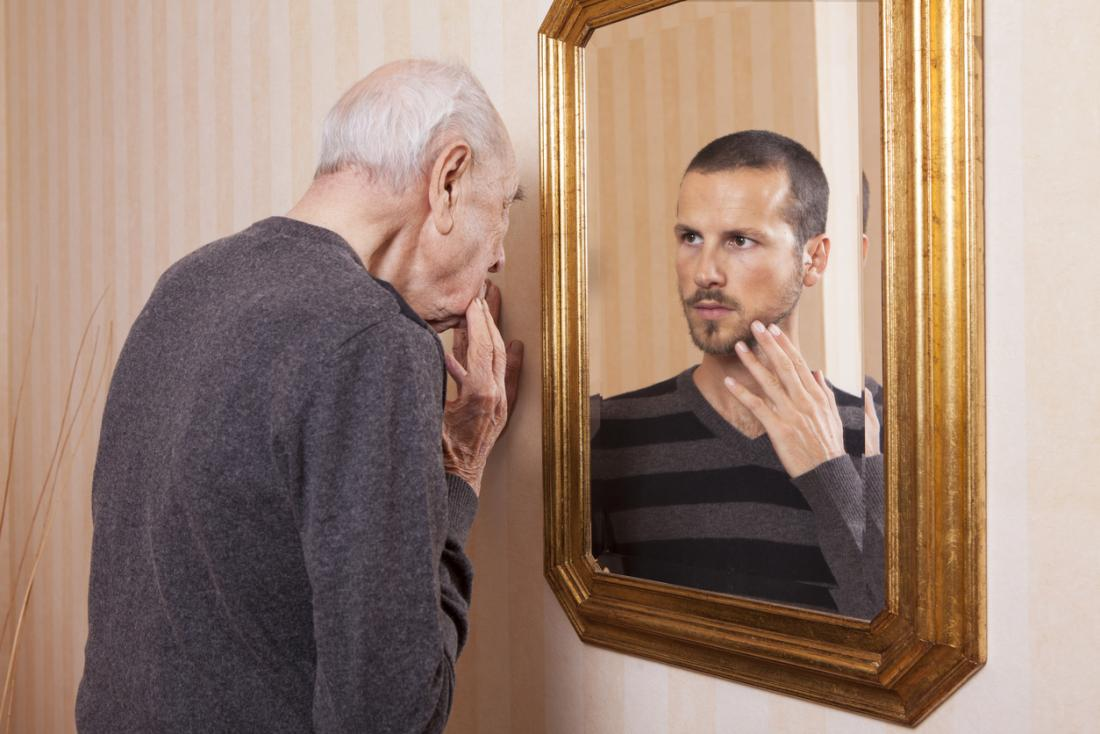 senior man looking at younger self reflection