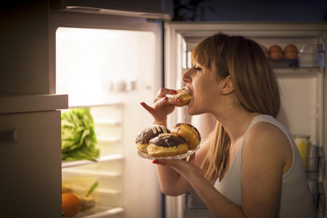 woman eating with fridge door open