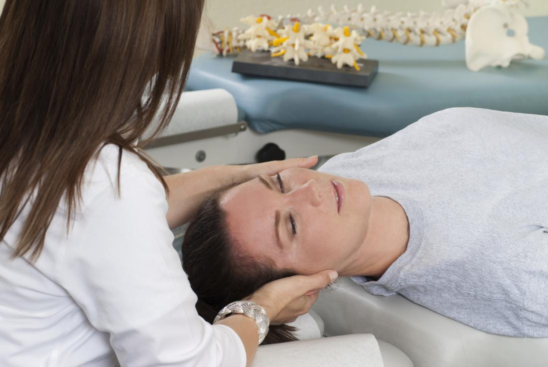Woman at chiropractors having a head and neck massage.