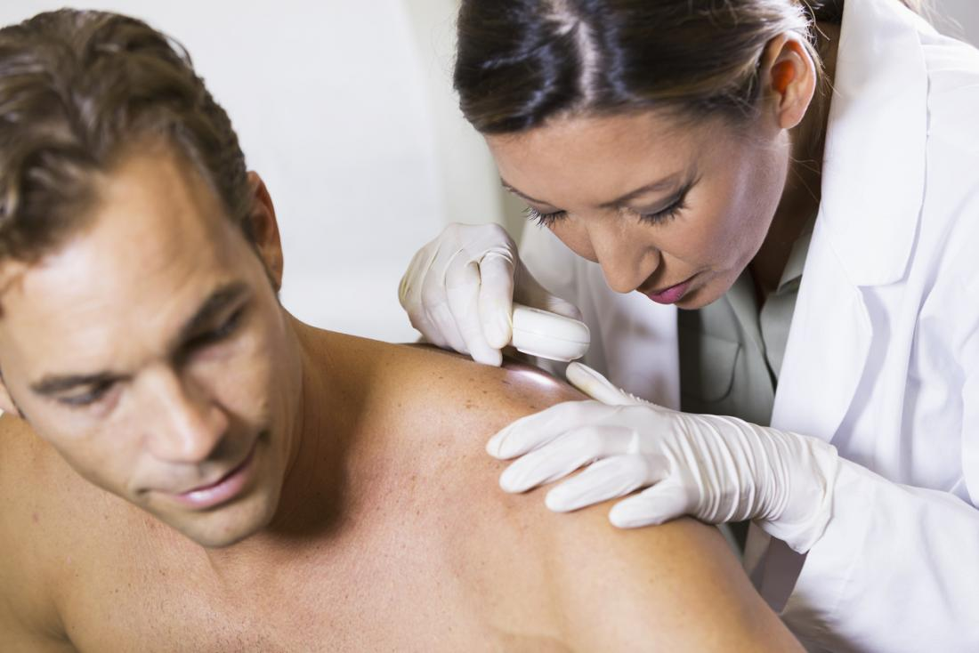 Dermatologist looks at a patients back