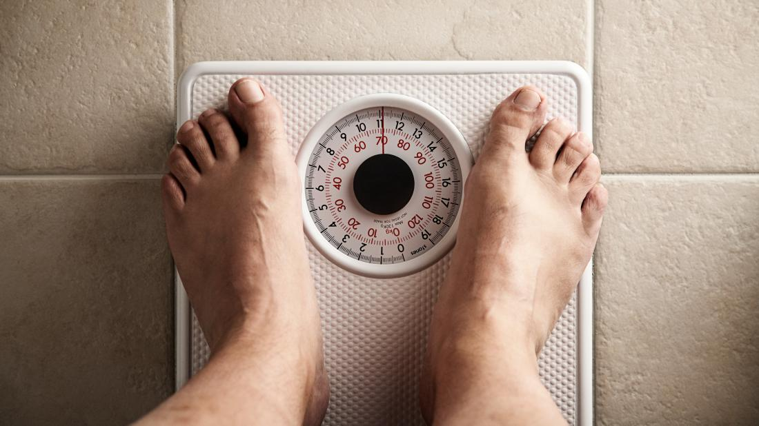 a mans feet on some scales as he is seeing if the keto diet is any good and made him lose weight