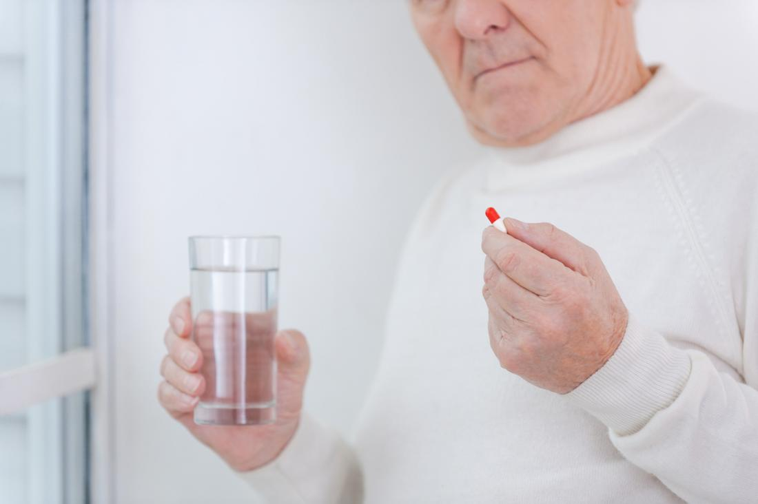 older man taking pill