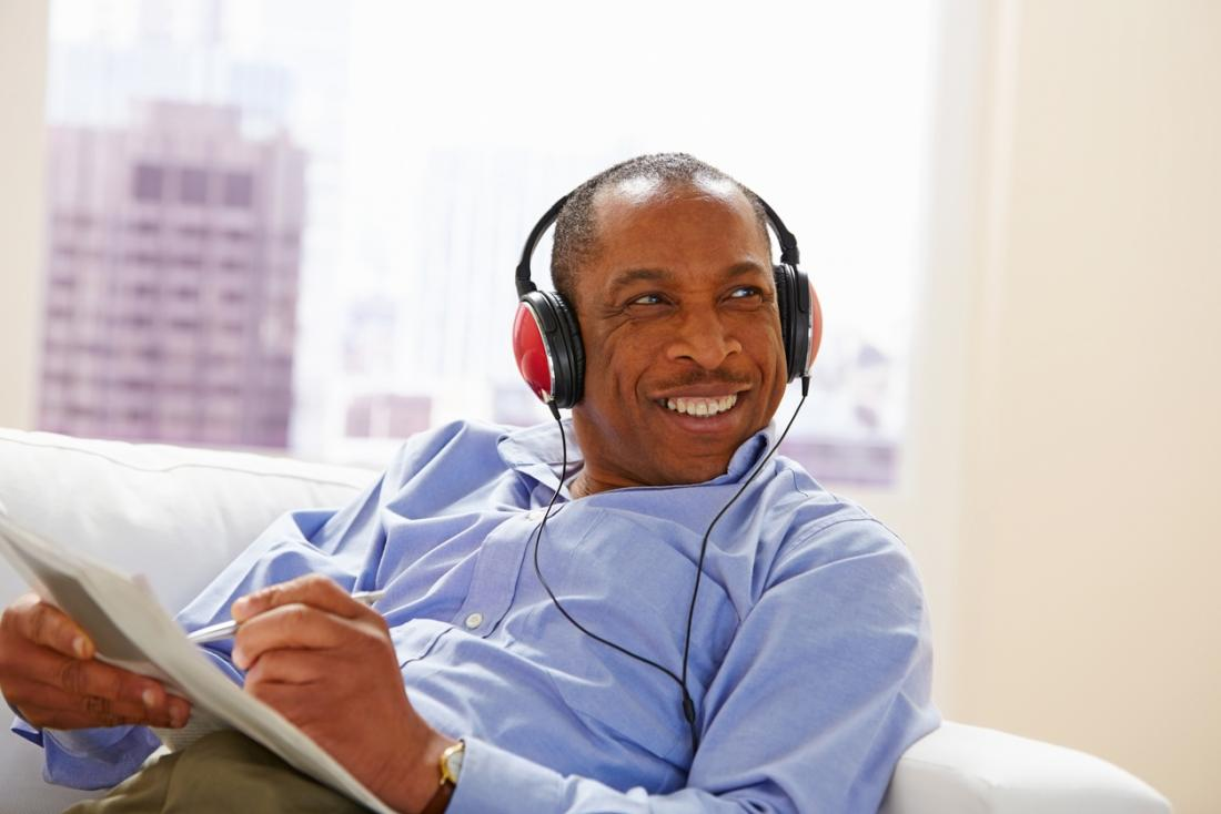 Happy man listening to music doing a puzzle