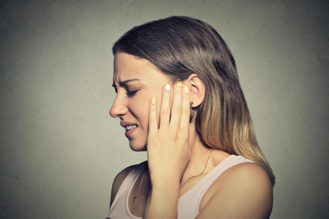 Woman holding her left ear in pain because of an infection.