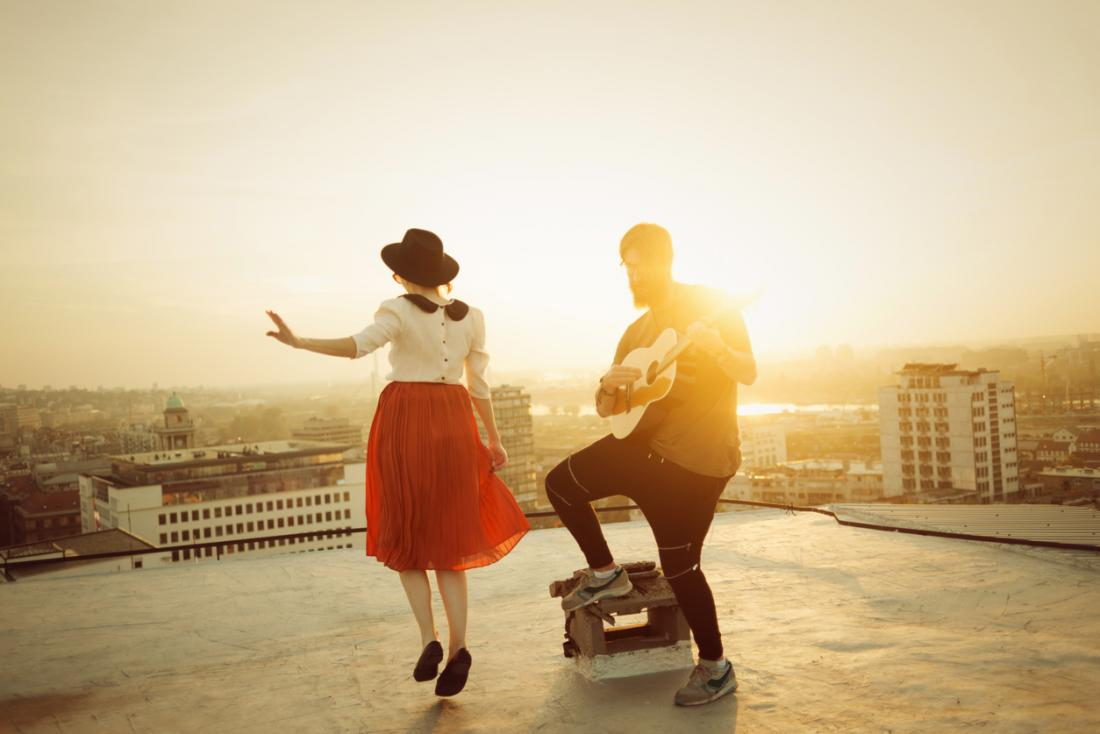 man playing guitar and woman dancing