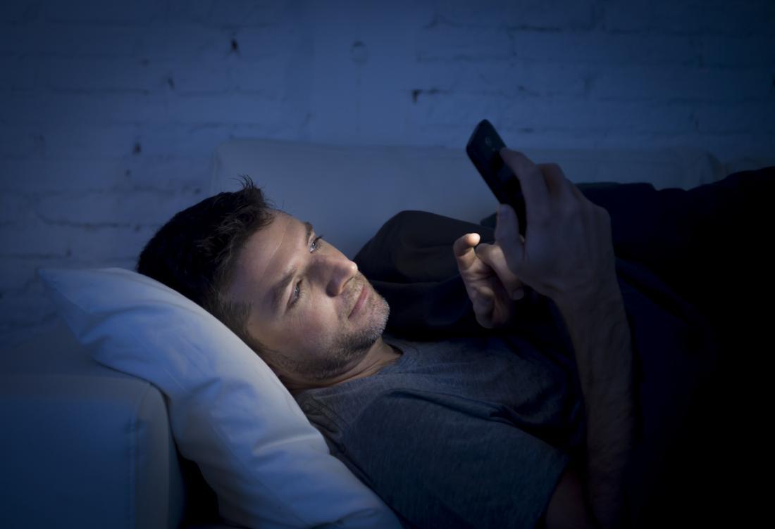 homem usando smartphone no escuro