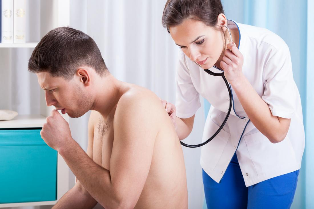 Shirtless male patient coughing while female doctor listens to his breathing using a stethoscope on his back.