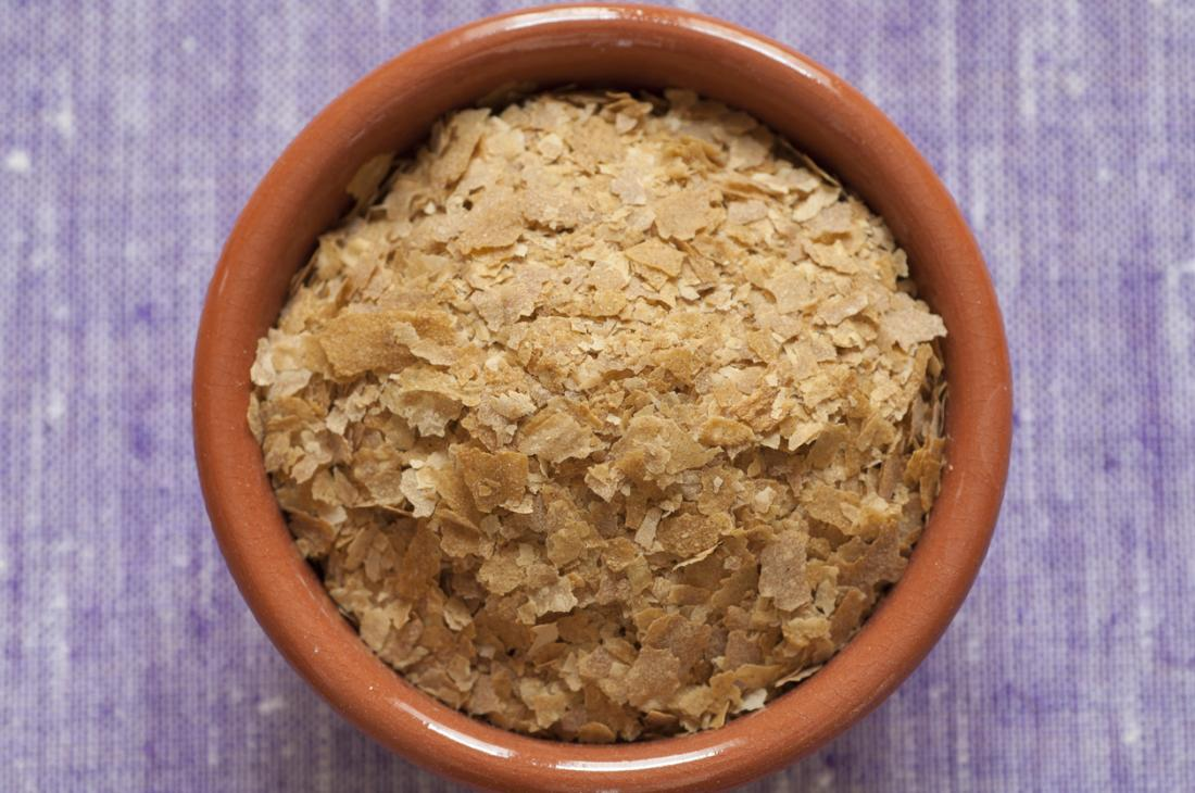 A bowl with nutritional yeast flakes, a plant-based source of B-12.