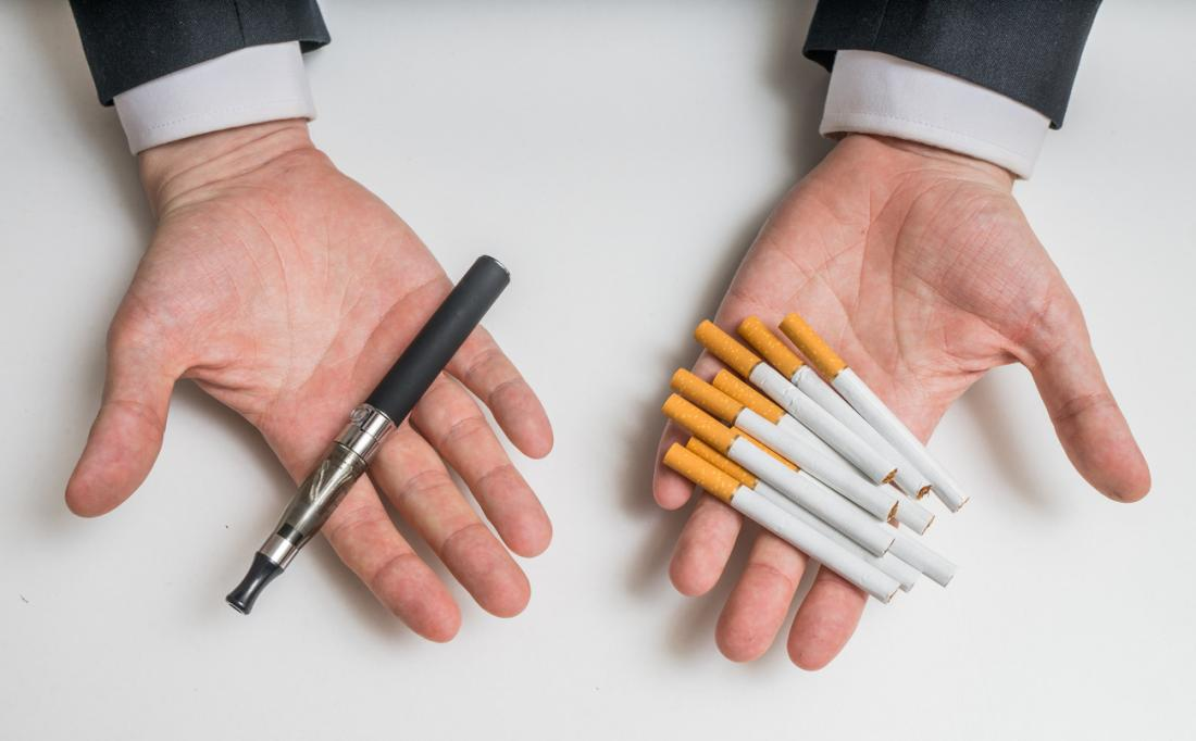 man comparing e-cigarette and cigarettes