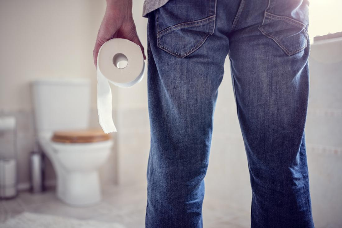 Man holding a roll of toilet roll as he enter the bathroom.