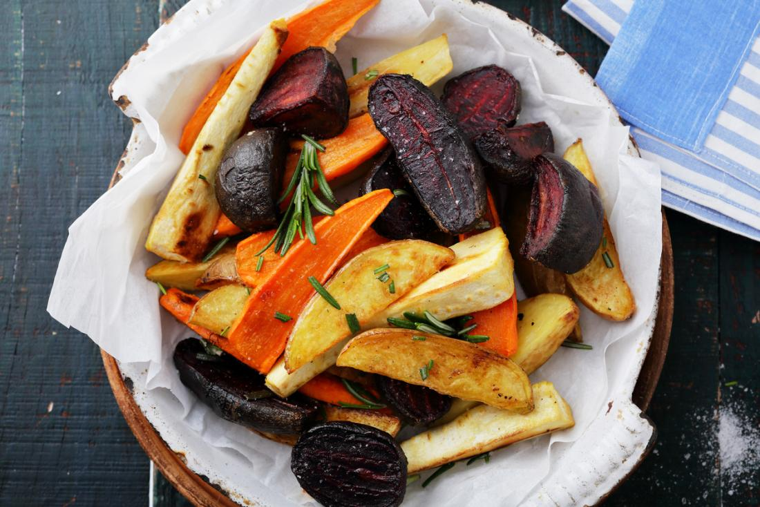 Roasted vegetables including potato, carrots, beetroot and parsnips in a bowl.