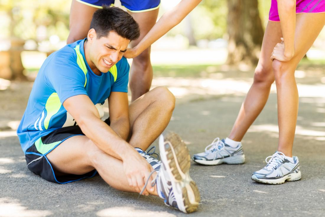 Man running kit sitting down holding his ankle in pain, whilst other joggers attend to him.