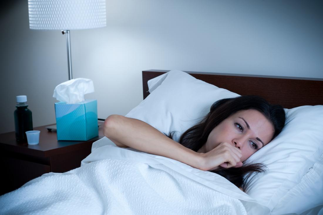 Woman coughing at night, with tissues and cough medicine by her bedside.