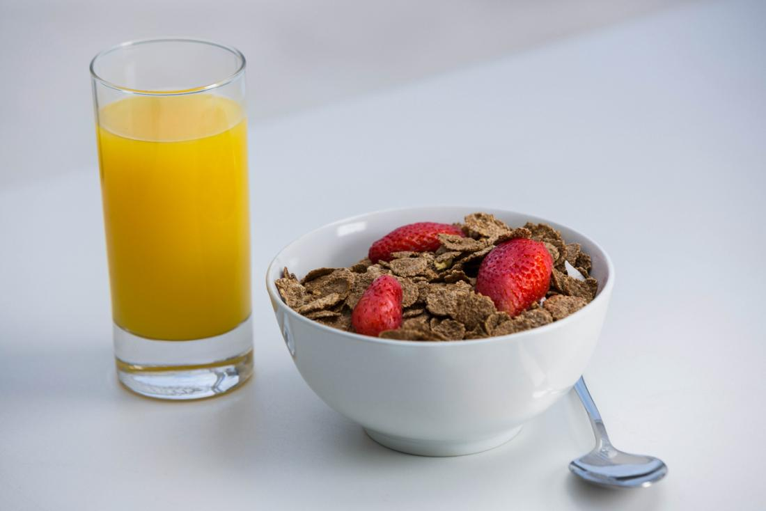 A bowl of bran flake cereal with strwberries on top, next to a glass of orange juice for breakfast.