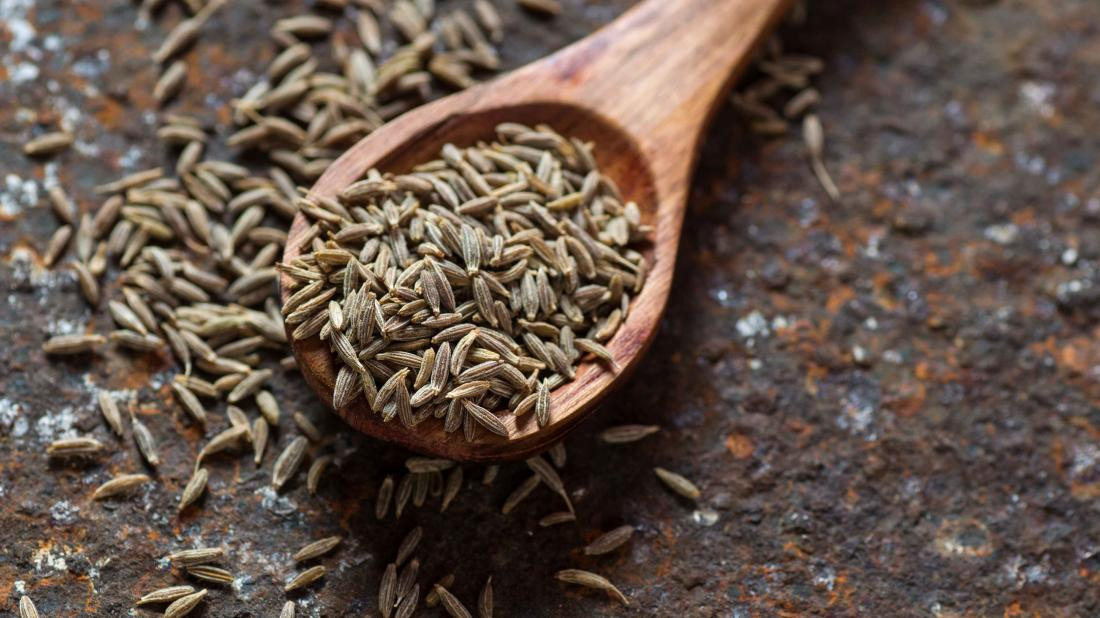 cumin seeds on a wooden spoon