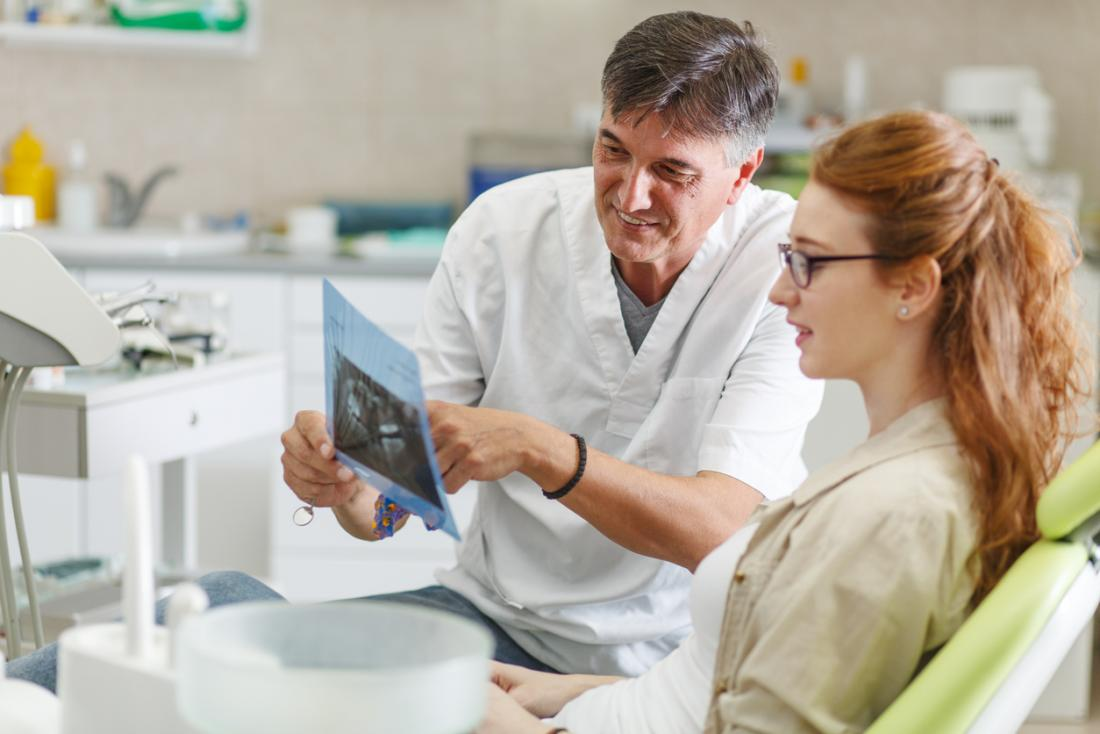 Male dentist with female patient, looking at an x-ray of her teeth and gums.