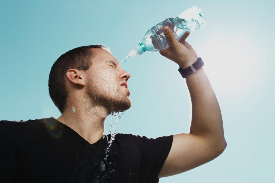 man pouring water on himself after exercise