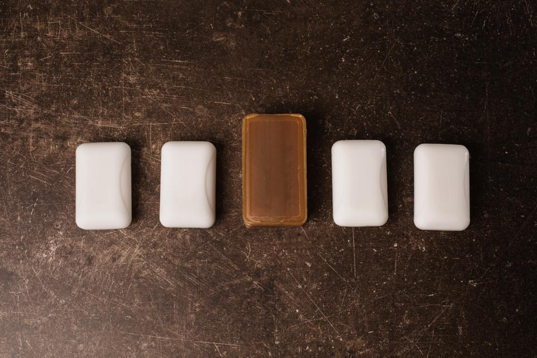 Four bars of white soap laid out, with one larger bar of tar soap in the middle.