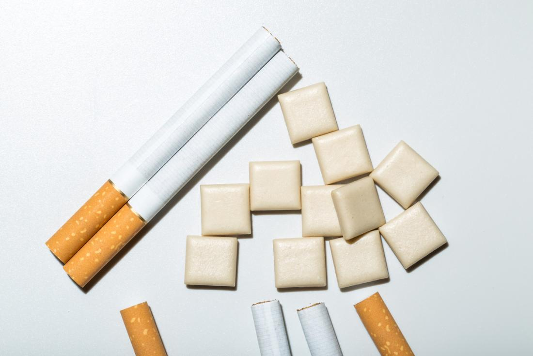 Cigarettes and nicotine gum on white background.