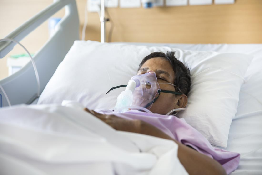 Patient in a hospital bed with a breathing ventilator.