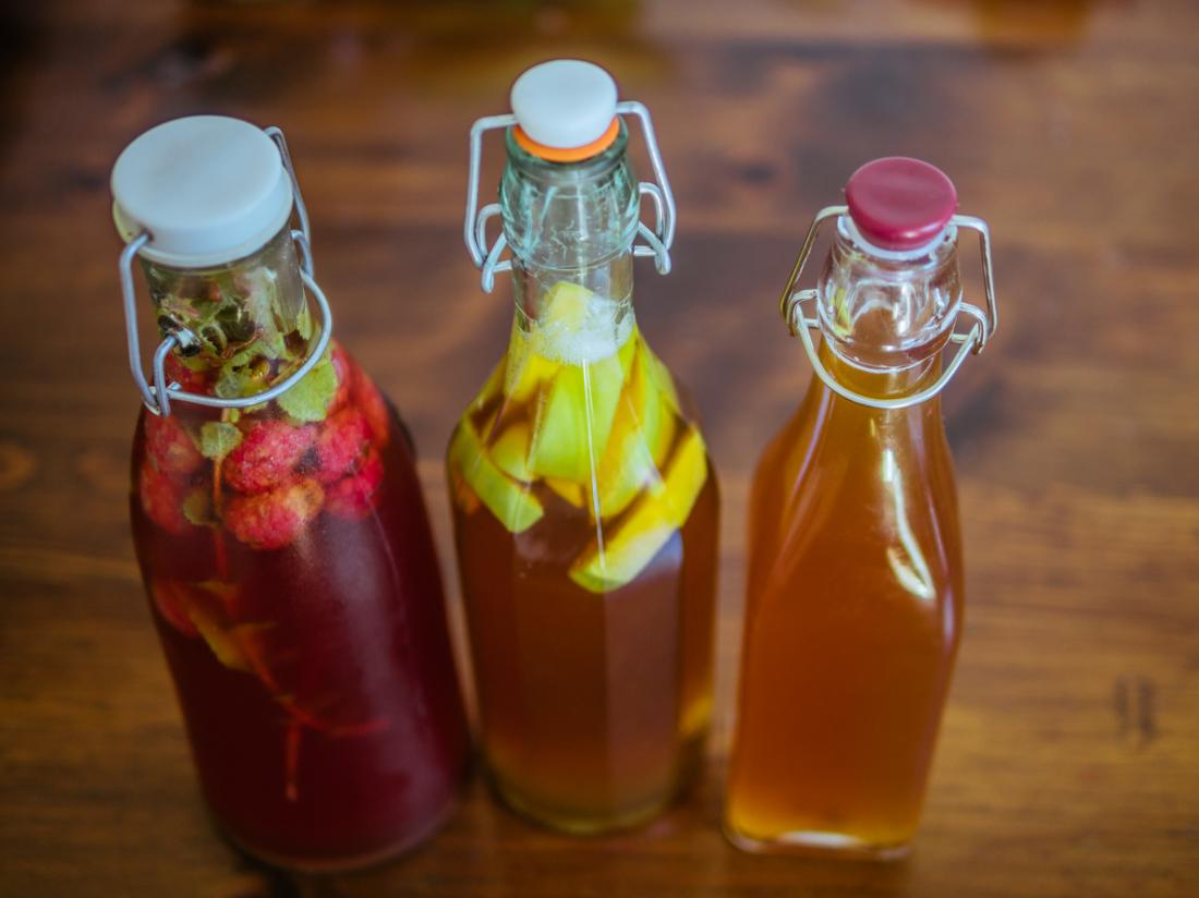 Kombucha tea in iced bottles, with fruit segments fermenting.