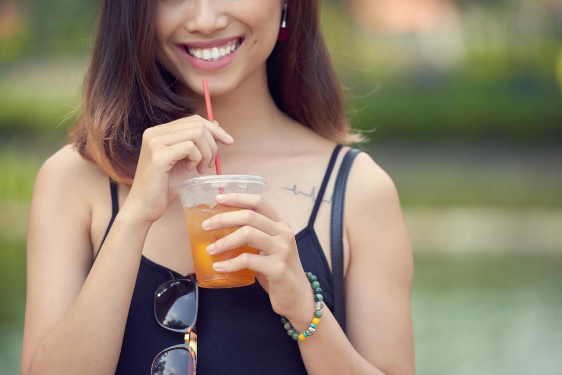 Young smiling woman drinking fruit juice ice tea.