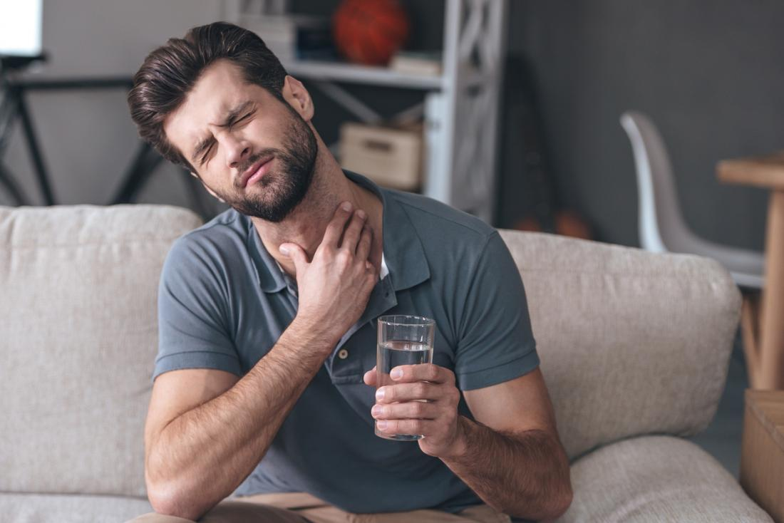Man with painful sore throat, holding a glass of water.