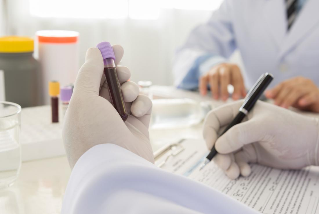 Phlebotomist examining vial with blood test sample, and filling out form.