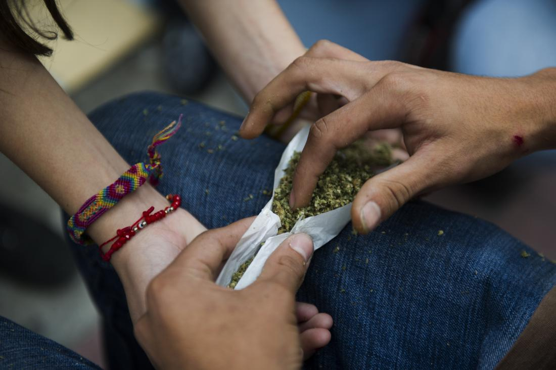 young people rolling a joint