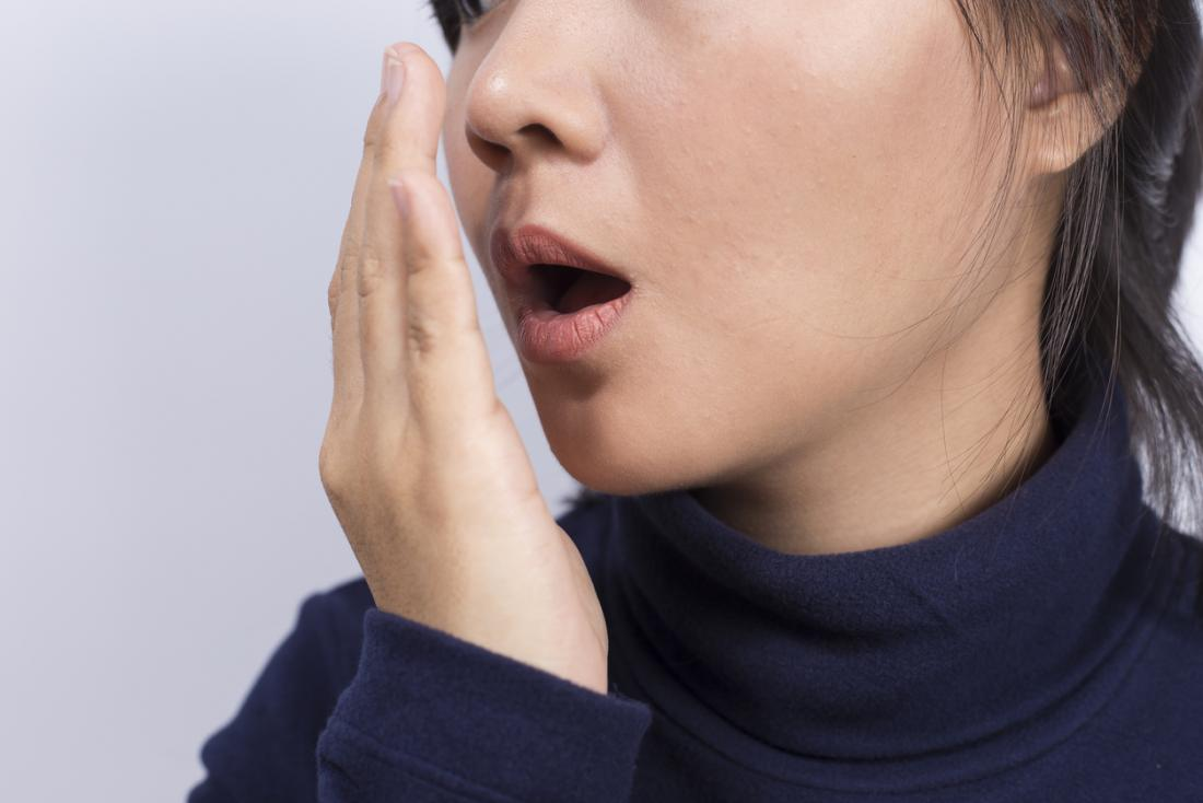 Woman checking how her breath smells by holding her hand in front of her mouth.