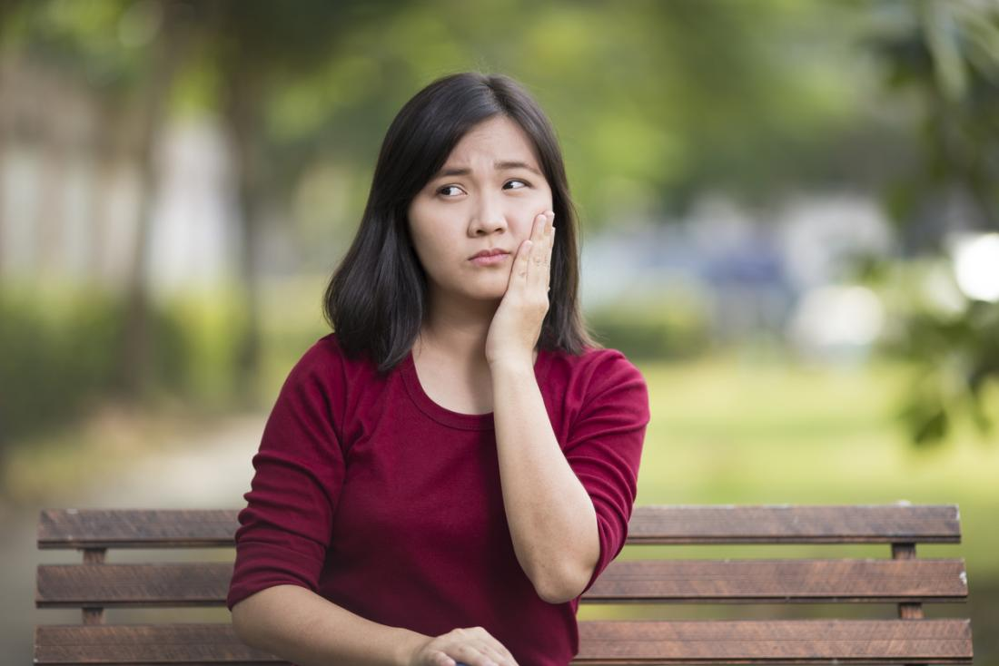 Woman sitting on a park bench holding her cheek in pain, because of a toothache or sore tongue.