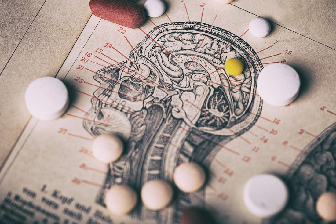 Different anti-psychotic pills, over diagram of human brain.
