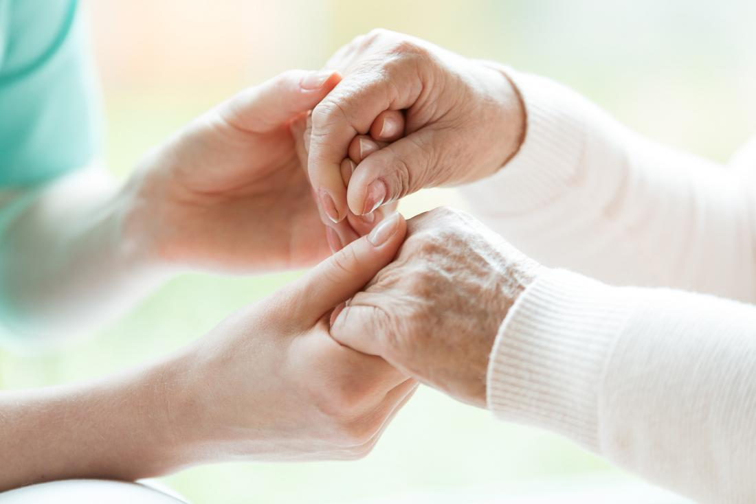 Senior with Parkinson's holding hands with nurse.