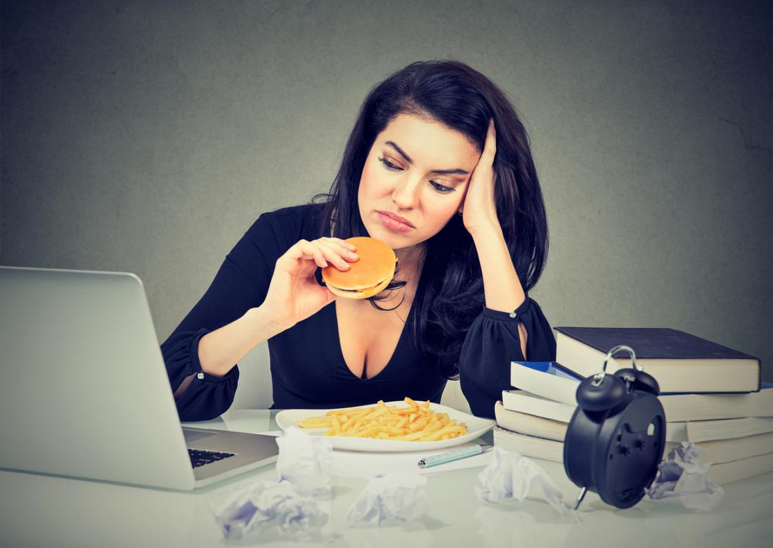 a woman eating a burger and chips at her desk