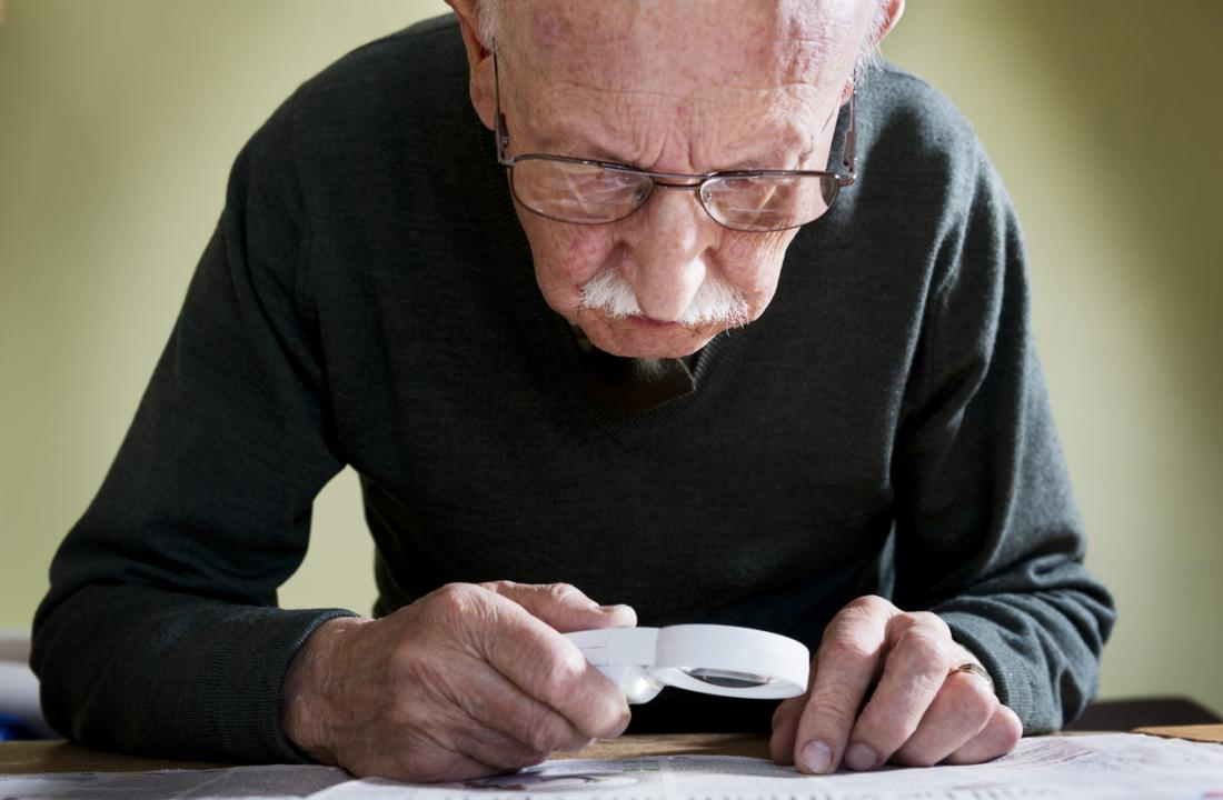 senior reading with magnifying glass