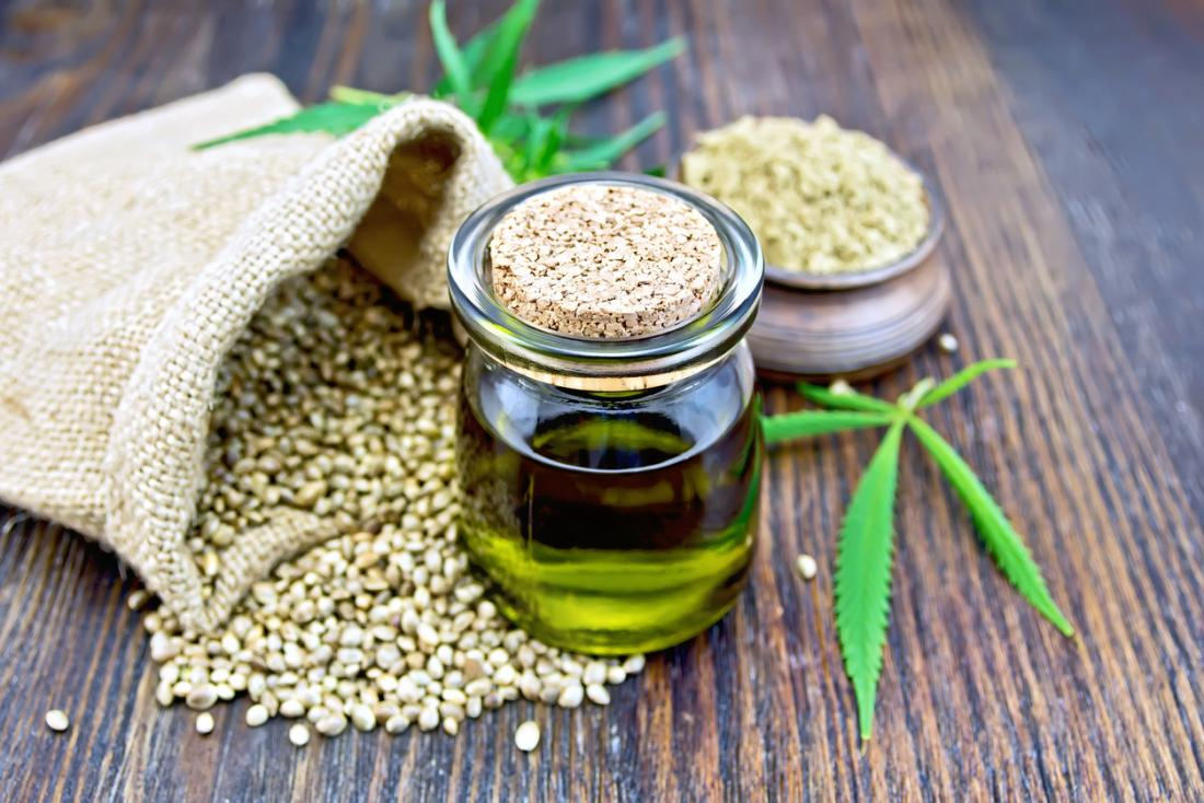 CBD hemp oil, in small clear jar with a bag of hemp seeds, marijuana leaves,