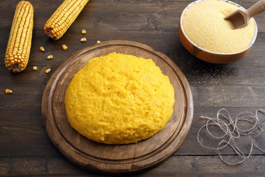Polenta on a wooden chopping board, with sweetcorn and corn grain on wooden table.