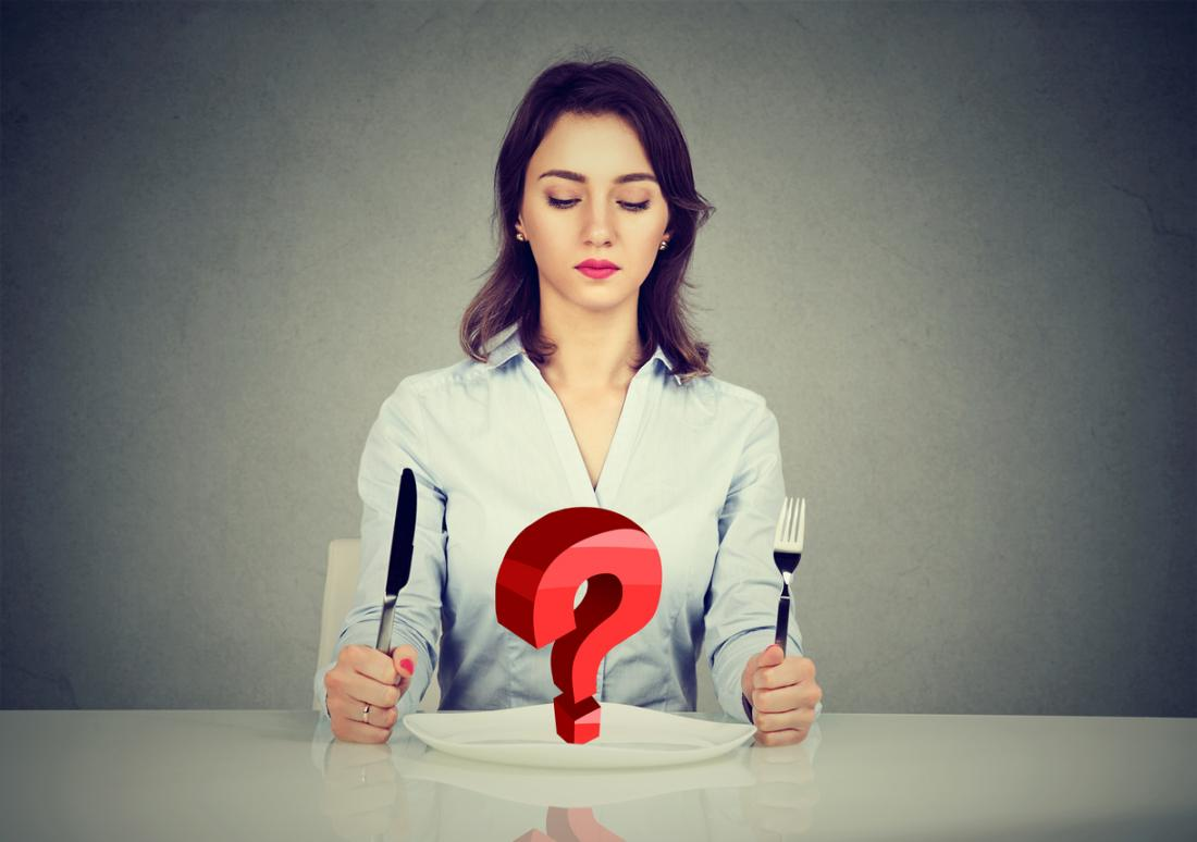 a woman looking at a plate with a question mark on it